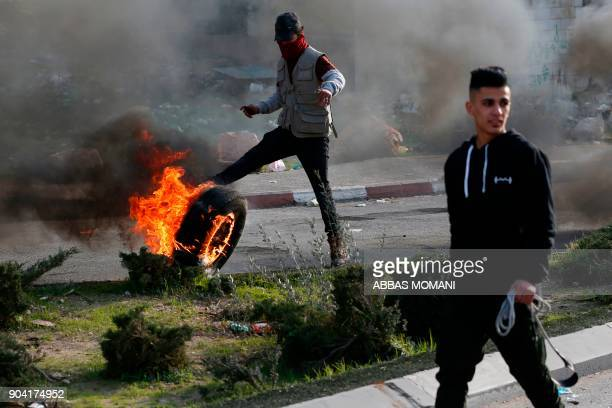 TOPSHOT Palestinian protesters burn tires during clashes with Israeli forces on January 12 2018 north of Ramallah in the Israelioccupied West Bank /...