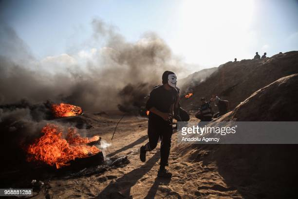 Palestinian protesters burn tyres after Israeli security forces' intervention during a protest organized to mark 70th anniversary of Nakba also known...