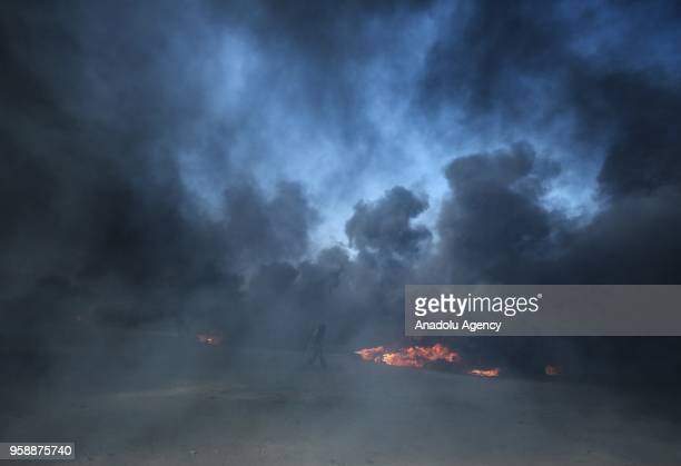 Palestinian protesters burn tyres and throw rocks with slingshots in response to Israeli security forces' intervention during a protest organized to...