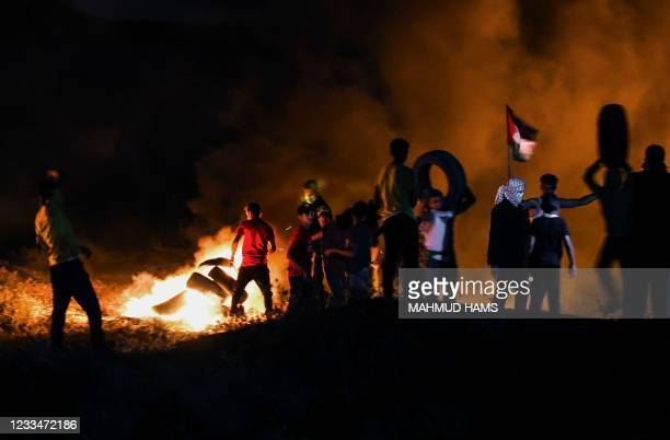Palestinian protesters burn tyres during a demonstration east of Gaza City by the border with Israel, on June 15 to protest the Israeli...