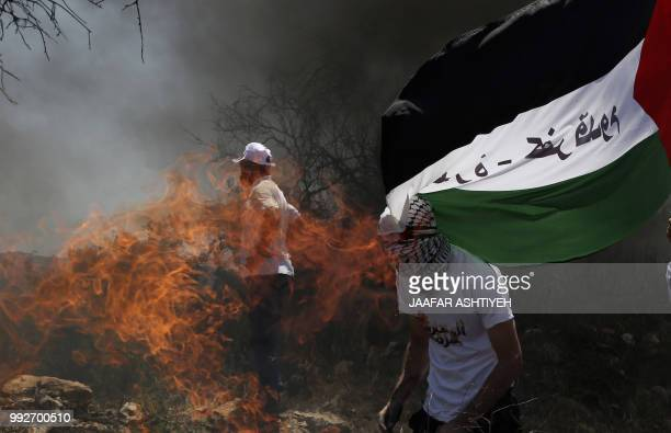 TOPSHOT Palestinian protesters burn tyres during a weekly demonstration against the expropriation of Palestinian land by Israel in the village of...