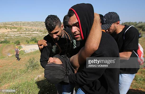 Palestinian protesters carry a comrade injured during clashes with Israeli security forces next to the Israeli Ofer prison in the West Bank village...