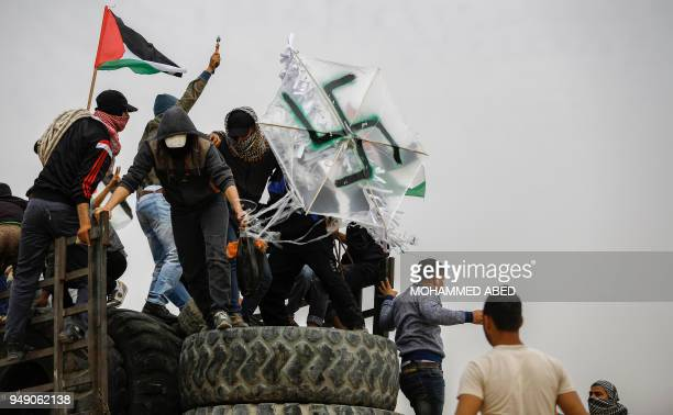 Palestinian protesters carry a transparent kite defaced with a swastika during clashes with Israeli forces across the border following a...