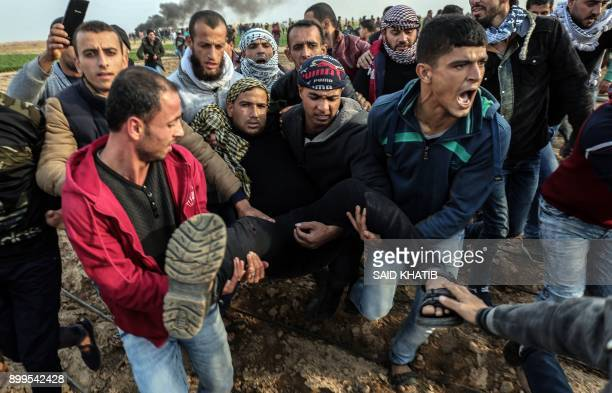 Palestinian protesters carry a wounded comrade during clash with Israeli forces near the Israel-Gaza border east of the southern Gaza strip city of...