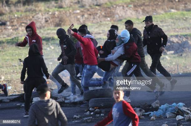 Palestinian protesters carry a wounded person as they clash with Israeli security forces during a demonstration against US President Donald Trump's...