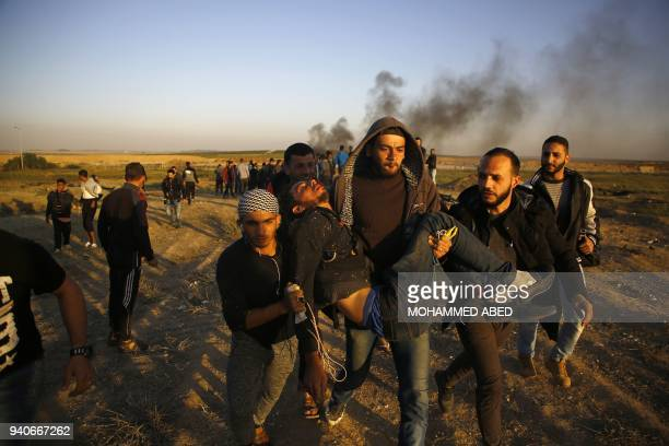 TOPSHOT Palestinian protesters carry an injured comrade during clashes with Israeli forces following a protest along the border with Israel east of...