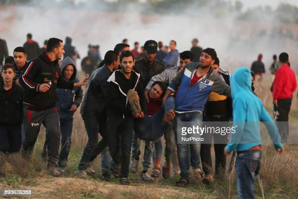 Palestinian protesters carry away an injured man during clashes with Israeli security forces following a protest against US President Donald Trump's...