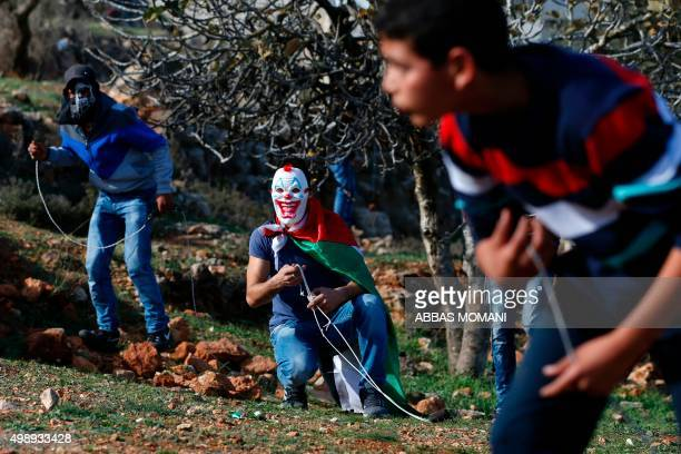 Palestinian protesters carry their slingshots during clashes with Israeli security forces on November 27 near the Israeli Ofer Military prison, near...