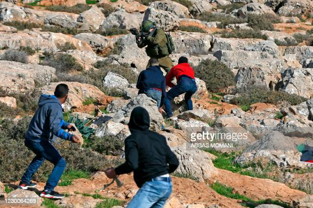 Palestinian protesters clash with an Israeli soldier following a rally in the village of Mughayir, north of the West Bank city of Ramallah, on...