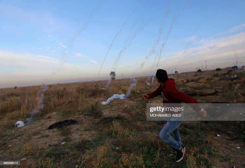 TOPSHOT - Palestinian protesters clash with Israeli forces on December 11, 2017 near the border fence with Israel, east of Gaza City. Protests flare in the Middle East and elsewhere over US President Donald Trump's declaration of Jerusalem as Israel's capital, a move that drew global condemnation and sparked days of unrest in the Palestinian territories. /