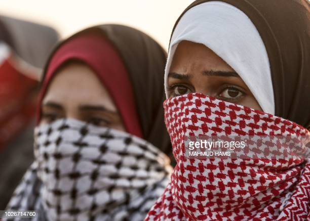 Palestinian protesters cover their faces look on during a demonstration near the Erez crossing with Israel on September 4 in the northern Gaza Strip...