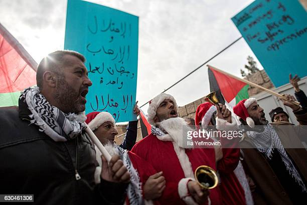 Palestinian protesters dressed as Santa Claus clash with Israeli security forces at the Israeli separation barrier on December 23 2016 in Bethlehem...