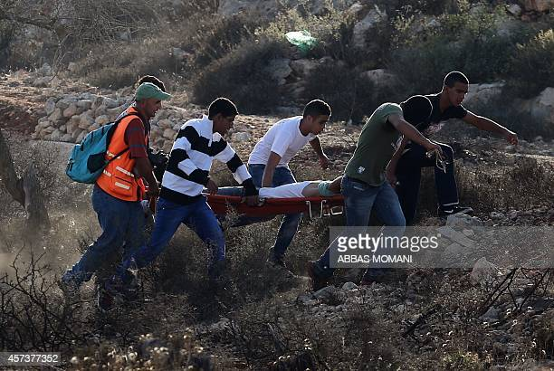 Palestinian protesters evacuate an injured comrade during clashes with Israeli security forces close to the Israeli Ofer military prison near the...