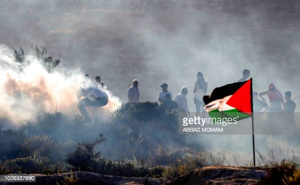 TOPSHOT Palestinian protesters flee from incoming tear gas canisters during clashes with Israeli security forces in the village of Ras Karkar west of...
