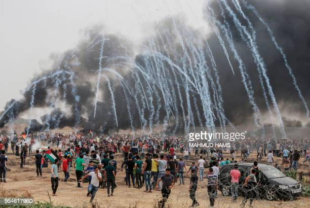 TOPSHOT Palestinian protesters flee from incoming teargas canisters during clashes with Israeli forces along the border with the Gaza strip east of...