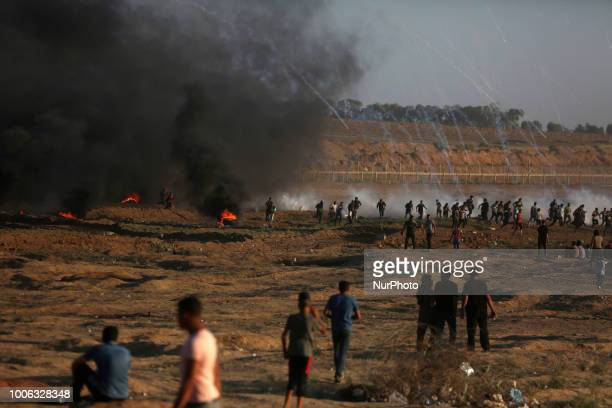 Palestinian protesters gather as tear gas canisters are launched by Israeli forces during a demonstration along the border between Israel and the...