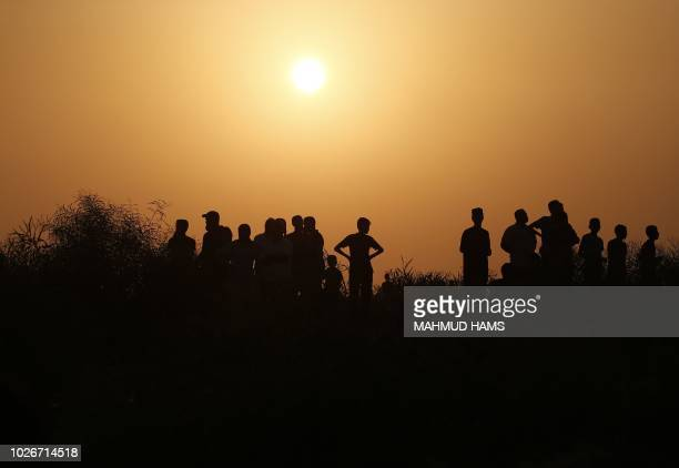 TOPSHOT Palestinian protesters gather at sunset during clashes with Israeli forces near the Erez crossing with Israel on September 4 in the northern...