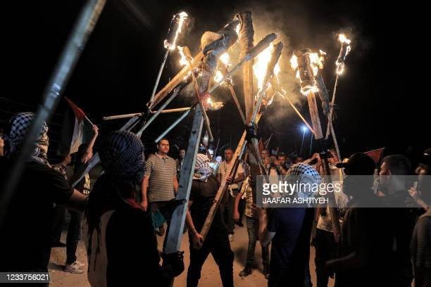 Palestinian protesters gather with torches during a demonstration against the Israeli settlers' outpost of Eviatar, in the town of Beita, near the...