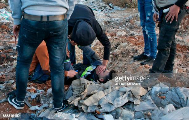 Palestinian protesters help a comrade suffocating from tear gas canisters fired by Israeli forces during clashes near an Israeli checkpoint in the...