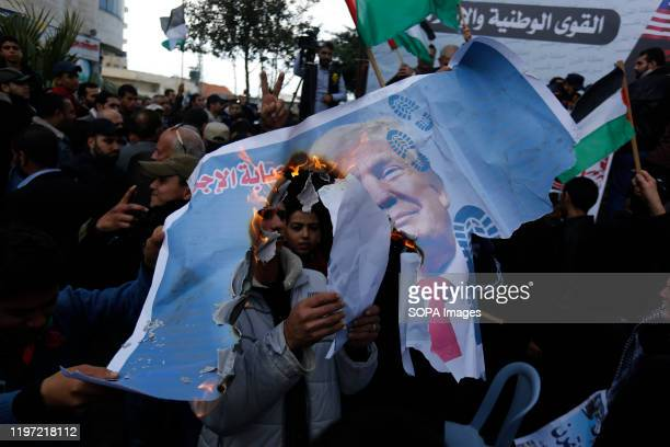 Palestinian protesters hold a torn posters depicting US President, Donald Trump during a protest against the US peace plan about the Middle East in...