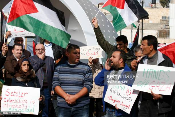 Palestinian protesters hold antiIsraeli signs and wave national flags on November 13 during a demonstration in the occupied West Bank town of Hebron...
