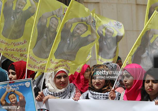 Palestinian protesters hold flags and placards bearing portraits of Fatah leader Marwan Barghuti during a march to mark the anniversary of his arrest...