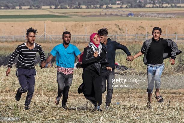 Palestinian protesters hold hands to protect a girl from shots as they run for cover during clashes with Israeli security forces following a...