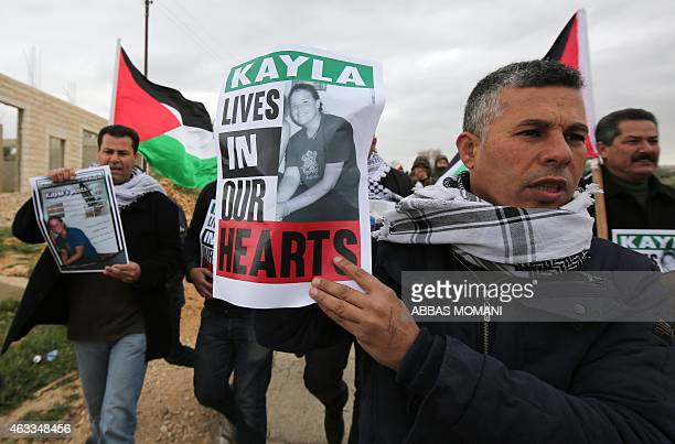 Palestinian protesters hold placard to protest against terrorism on February 13 2015 before a demonstration against Jewish settlements in the West...