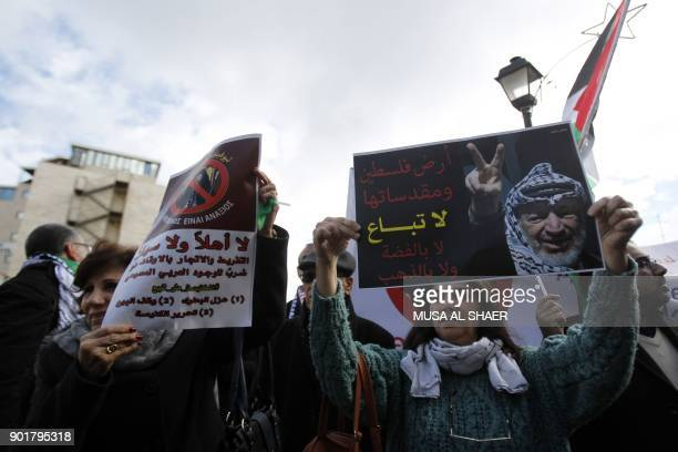 Palestinian protesters hold placards as the convoy of Jerusalem's Greek Orthodox patriarch Theophilos III arrives in the West Bank town of Bethlehem...