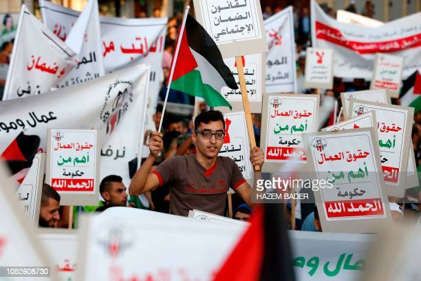 Palestinian protesters hold placards reading the rights of workers are more important than the government as they demonstrate against the decision of...