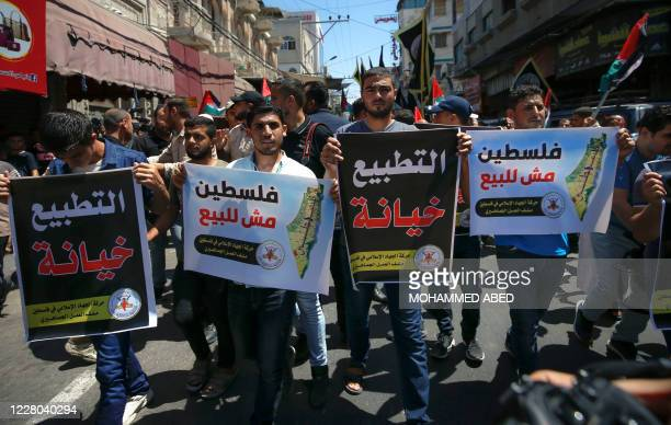 Palestinian protesters hold slogans reading in Arabic normalisation is betrayal and Palestine is not for sale during a demonstration in Gaza City on...
