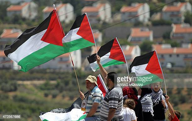 Palestinian protesters hold their national flags during clashes with Israeli security forces following a demonstration against Palestinian land...
