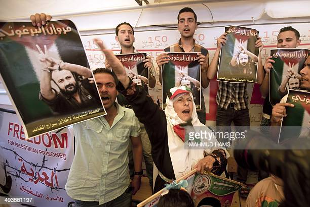 Palestinian protesters hold up pictures of Marwan Barghuti one of the leaders of the second Palestinian intifada or uprising who has been in prison...