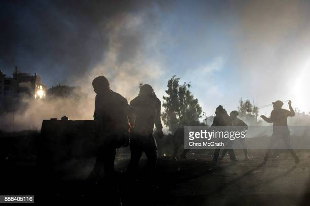 Palestinian protesters hurl rocks at Israeli border guards during clashes near an Israeli checkpoint on December 8 2017 in Ramallah West Bank At...