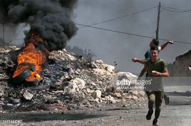 TOPSHOT Palestinian protesters hurl stones at Israeli forces during clashes following a weekly demonstration against the expropriation of Palestinian...