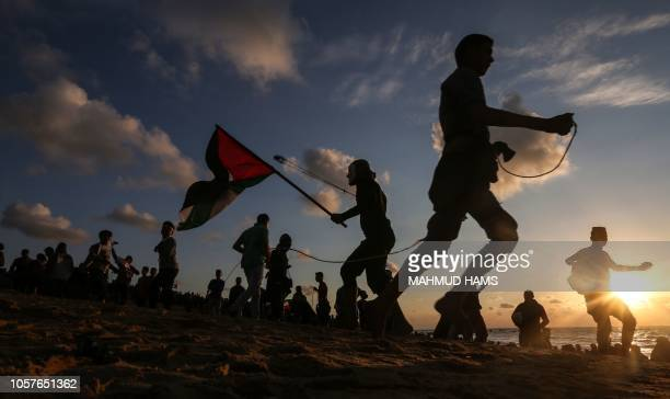 TOPSHOT Palestinian protesters hurl stones during a demonstration calling for an end to the Israeli blockade on Gaza on a beach in Beit Lahia near...
