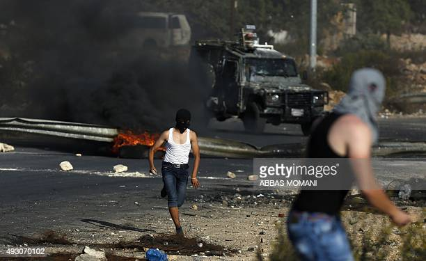 Palestinian protesters hurl stones during clashes with Israeli security forces near the Beit El settlement on the outskirts of Ramallah in the West...