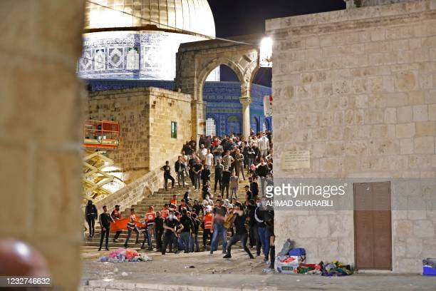 Palestinian protesters hurl stones during clashes with Israeli police at the al-Aqsa mosque compound in Jerusalem, on May 7, 2021.