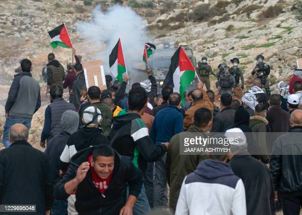 Palestinian protesters lift national flags amid clashes with Israeli security forces following a demonstration against the expansion of settlements...