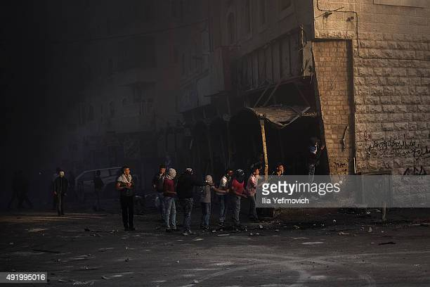 Palestinian protesters line up as they clash with Israeli border police on October 9, 2015 in Shuafat refugee camp in Jerusalem, Israel. As tension...