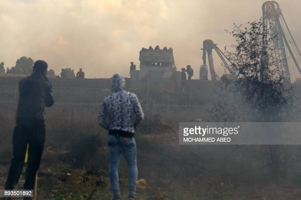 Palestinian protesters look at Israeli security forces standing guard at an outpost next to heavy machinery on the other side of the border fence...