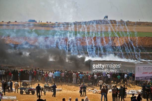 TOPSHOT Palestinian protesters look at tear gas and smoke billowing from burning tyres east of Gaza City on May 14 as Palestinians readied for...