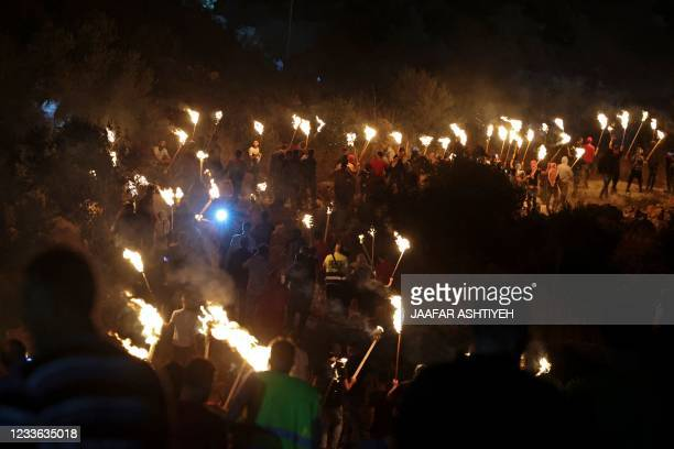 Palestinian protesters march with torches during a demonstration against the newly built Israeli settlers' outpost of Eviatar in the town of Beita,...