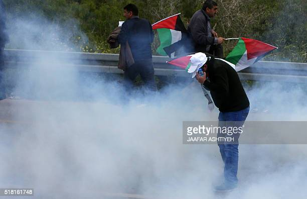 Palestinian protesters protect themselves from tear gas smoke during clashes with Israeli security forces following a demonstration to mark Land Day...
