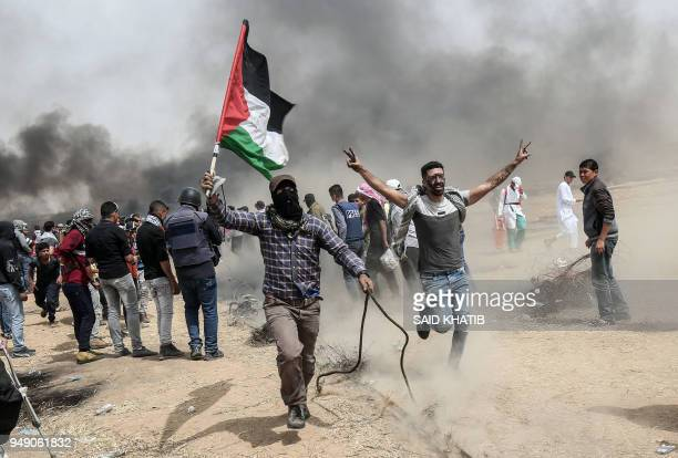 TOPSHOT Palestinian protesters pull a metal cable as they try to take down a section of barbed wire during clashes with Israeli forces on April 20...