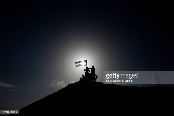 TOPSHOT Palestinian protesters raise the national flag during clashes with Israeli soldiers near the border fence east of Gaza City on February 23...