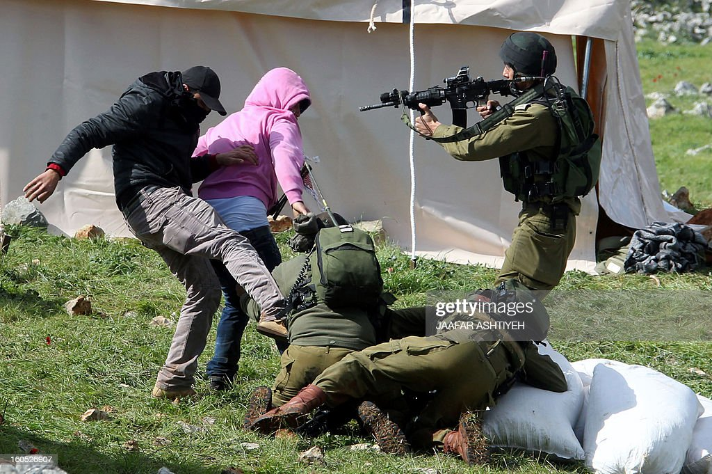 Palestinian protesters resist arrest by Israeli soldiers as they forcefully remove demonstrators from a new camp set up to protest against Jewish settlements near the West Bank village of Burin on February 2, 2013. An AFP correspondent said the Israeli army used tear gas and violence to remove hundreds of people who had set up four temporary huts and three tents near Burin, south of Nablus in the occupied West Bank.