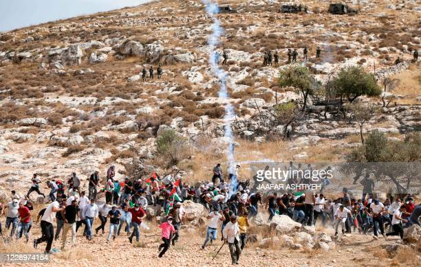 Palestinian protesters run amidst tear gas smoke during clashes with Israeli security forces following a demonstration against the expansion of...