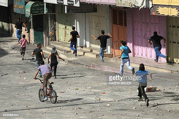 Palestinian protesters run away to take cover during clashes with Israeli security forces in the city center of the West Bank town of Hebron on...