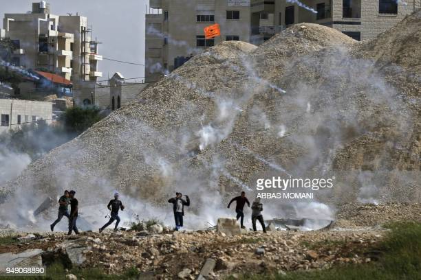 TOPSHOT Palestinian protesters run for cover from an incoming teargas volley during clashes with Israeli forces following a demonstration near the...